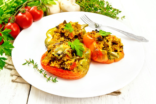Pepper stuffed with mushrooms and couscous in white plate on table