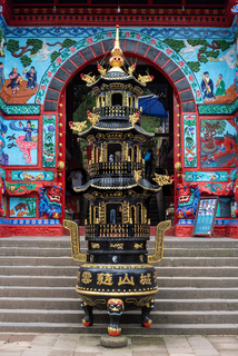 Incense burner in front of a colorful temple gate.