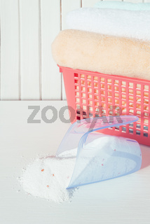 Bath towels and washing powder in measuring cup