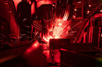 Welder in mask welding metal authentic shooting through red safety glass.