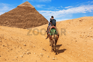 Tourists riding camels near the Pyramid of Khafre, Giza