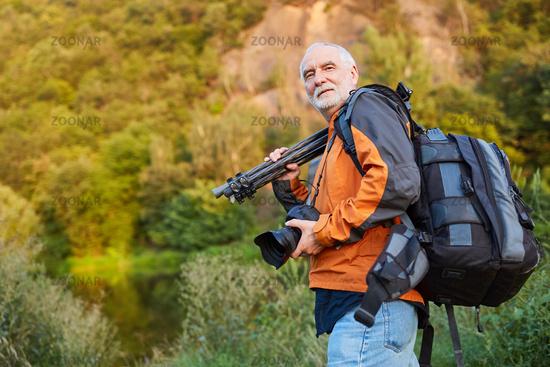 Professioneller Fotograf mit Kamerarucksack und Stativ