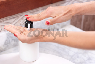Female hands applying liquid soap, close up.