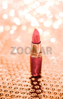 Coral lipstick on rose gold Christmas, New Years and Valentines Day holiday glitter background, make-up and cosmetics product for luxury beauty brand