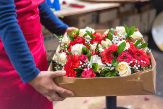 Female Florist holding a box with beautiful flowers for delivery.