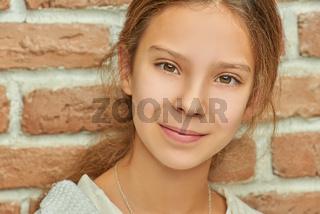 Little beautiful smiling girl near brick wall