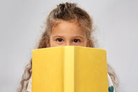 little girl hiding behind yellow book