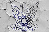 coat of arms of Israeli Air Force painted on cracked wall