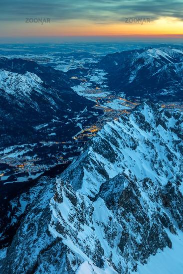 Daybreak on Zugspitze mountain summit with a view to illuminated Garmisch Partenkirchen and Loisach
