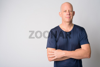 Portrait of mature handsome bald man with arms crossed