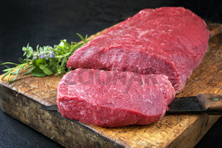 Raw roast beef with herbs offered as closeup on an old rustic wooden cutting board