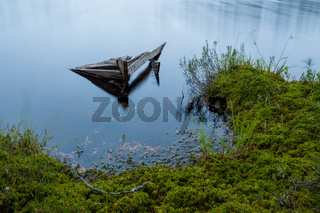 Sunken rowboat abandoned in small forest lake