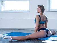 In gym. Sexy girl posing while doing leg split