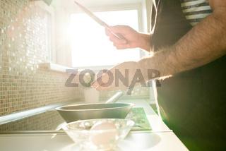 Man cracking egg above cooking pan