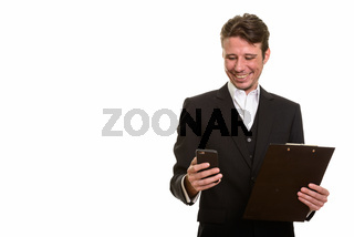 Happy Caucasian businessman using mobile phone while holding cli