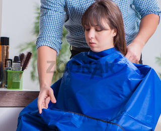 Man male hairdresser doing haircut for woman