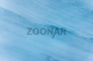 Close-up blurred wall of a centuries-old glacier with a structure of stripes and bubbles. Ice blue light texture