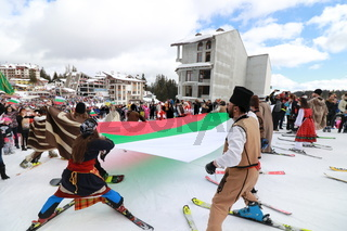 Skiing with Bulgarian flags at Pamporovo ski resort, Bulgaria. People dressed with traditional Bulgarian clothes skiing with the national flag.