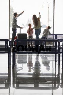 Familie im Wartebereich des Flughafens am Fenster