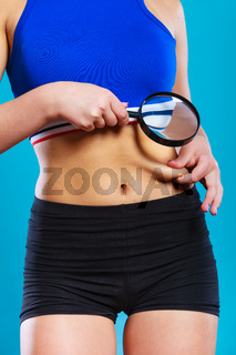 Woman pinches her waist examining it with magnifying glass