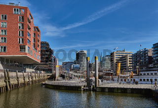 Modern buildings with offices and appartments embrace a little port with historic ships at new harbor city of Hamburg.