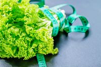 fresh green lettuce salad leaves with measuring tape on dark background. The concept of a healthy lifestyle, diet, healthy food.