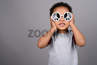 Young cute African boy against gray background