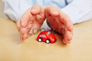 Hände schützen Auto als Symbol für KFZ-Versicherung