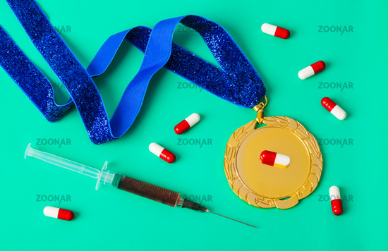 Gold medal with syringe and pills on green