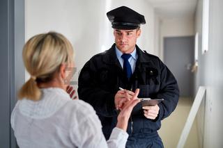 Polizist redet mit Frau bei Zeugenbefragung