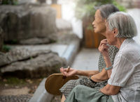 Two old retired chinese asian women sitting in a park