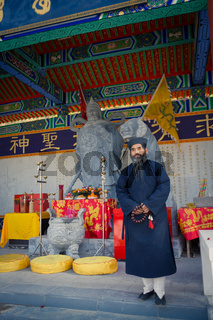 XIAN, CHINA - SEP 06, 2013: Middle-aged Taoist priest wears a silken, black Manchurian hat and a traditional deep-blue Taoist priest suit
