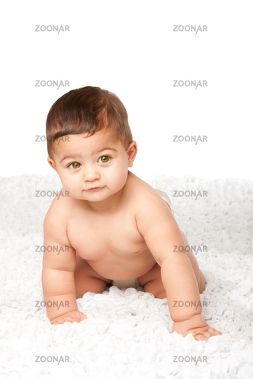 Cute baby infant with big green eyes crawling on white