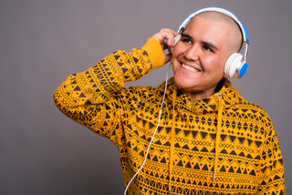 Young bald Asian man listening to music against gray background