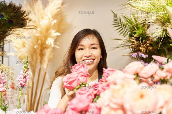 Asiatische Frau als Florist mit vielen Blumen