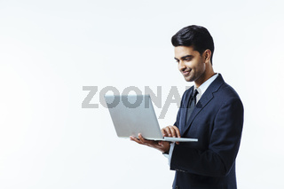 Portrait of a confident young man entrepreneur in business suit working on a laptop
