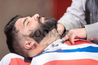 Handsome man having a shave with vintage razor at the barbershop.