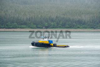 small tug boat on the move at bay in alaska