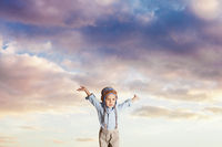 Kid pretending flying on a cloudy sky background