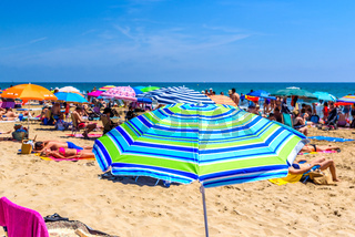 Valencia, Spain - June 23, 2019: Agglomeration of holiday people taking advantage of the sand of a Mediterranean beach to place their umbrellas and enjoy the summer.