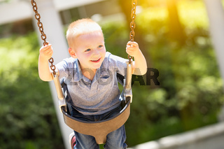 Happy Young Boy Having Fun On The Swings At The Playground
