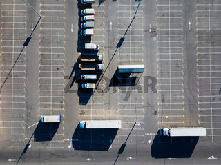 Aerial view from a drone of a parking lot with a multitude of trucks on a sunny day. Top view