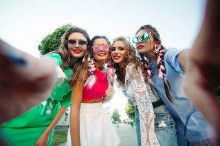 Four fashionable and beautiful best girlfriends in glasses, posing do general self for social networks, lifestyle, spend time fun. Women in sunglasses after shopping and beauty salon