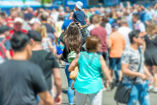 Woman with smartphone and child in crowd