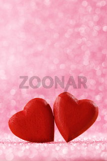 Two red hearts on bokeh background