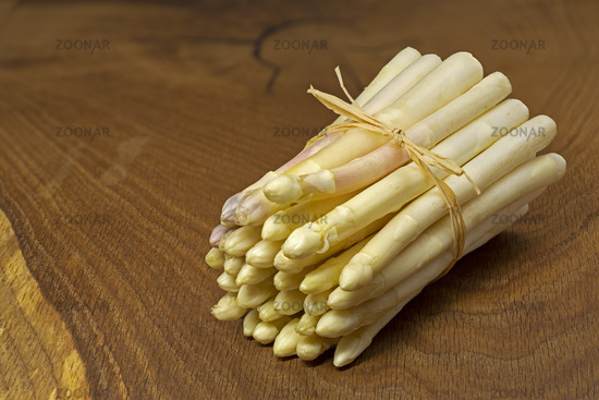 bunch of fresh white asparagus on wooden boards
