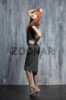 Young beautiful redhead lady posing in studio