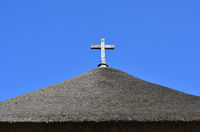 Wooden cross on a thatched roof of a chapel