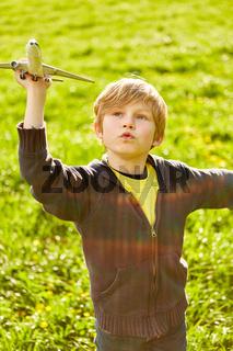 Junge lässt in seiner Fantasie ein Flugzeug fliegen