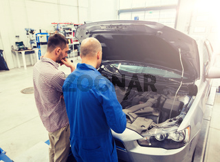 auto mechanic and man or car owner at workshop